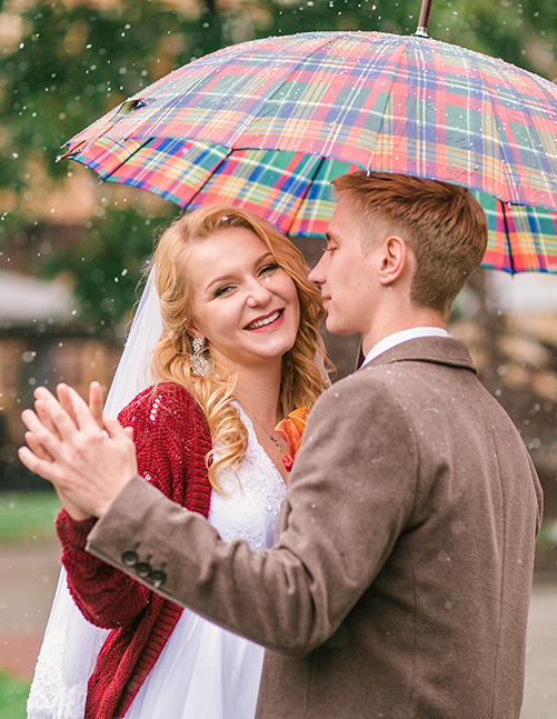 Young beautiful couple bride and groom in the snow with an umbre